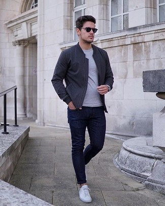 Men's Outfits 2020: This casual pairing of a charcoal vertical striped bomber jacket and navy skinny jeans is extremely versatile and up for any adventure you may find yourself on. Go ahead and add white canvas low top sneakers to the equation for a dash of elegance.