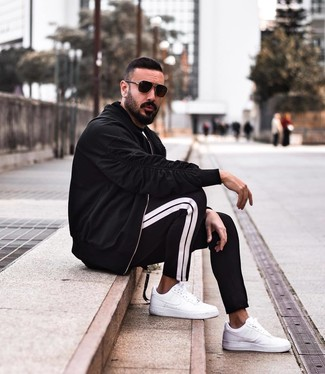 How to wear: black bomber jacket, black crew-neck t-shirt, black and white sweatpants, white leather low top sneakers