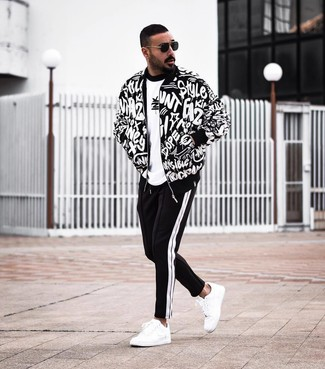 How to wear: black and white print bomber jacket, white and black print crew-neck t-shirt, black and white sweatpants, white leather low top sneakers