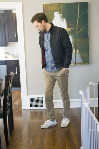 How To Wear a Denim Shirt With a Bomber Jacket In Spring For Men: This getup with a bomber jacket and a denim shirt isn't a hard one to achieve and is easy to change according to circumstances. Feeling venturesome? Tone down your ensemble by finishing with white canvas low top sneakers. You can bet this combo will become your favorite come warmer weather.