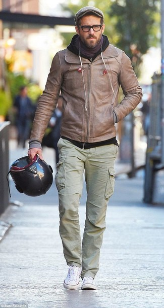 How to wear: beige leather bomber jacket, black hoodie, olive cargo pants, white canvas low top sneakers