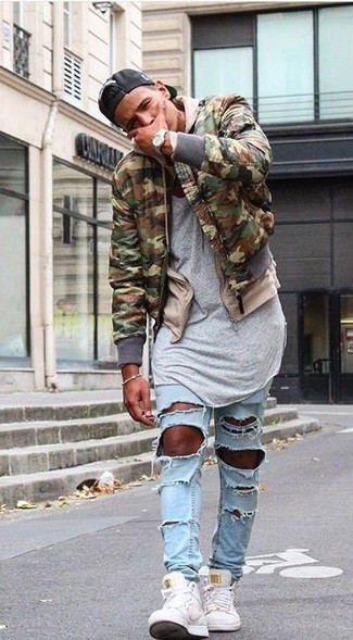 How to wear: olive camouflage bomber jacket, beige hoodie, grey crew-neck t-shirt, light blue ripped skinny jeans
