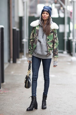 How to wear: green camouflage bomber jacket, grey hoodie, navy skinny jeans, black leather lace-up ankle boots