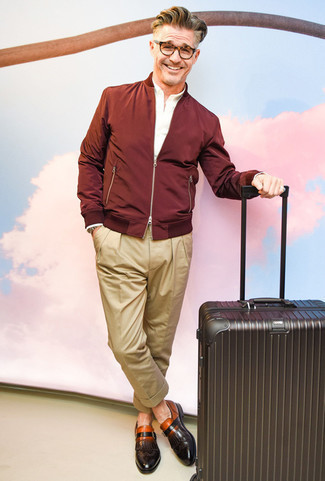 How to Wear a Burgundy Bomber Jacket For Men: A burgundy bomber jacket and khaki chinos are a smart combo worth having in your day-to-day wardrobe. Infuse this outfit with a dash of refinement by wearing a pair of dark brown leather monks.