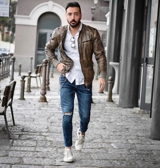 How to wear: brown leather bomber jacket, white long sleeve shirt, blue ripped skinny jeans, white low top sneakers