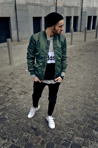 How to Wear a Dark Green Bomber Jacket For Men: This off-duty pairing of a dark green bomber jacket and black ripped jeans is very easy to throw together without a second thought, helping you look on-trend and ready for anything without spending too much time combing through your wardrobe. For something more on the elegant side to finish off this outfit, add a pair of white leather low top sneakers to your getup.