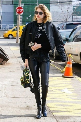 How to wear: black bomber jacket, black and white print sweatshirt, black leather leggings, black leather ankle boots