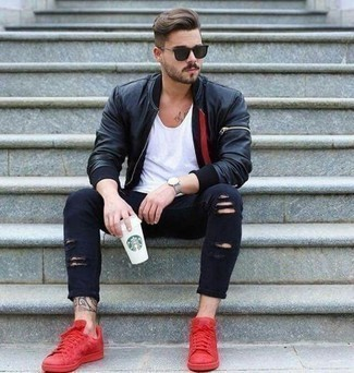 Navy Ripped Skinny Jeans Outfits For Men: Uber stylish and functional, this combo of a black leather bomber jacket and navy ripped skinny jeans will provide you with wonderful styling opportunities. Puzzled as to how to round off your getup? Rock red suede low top sneakers to ramp up the wow factor.