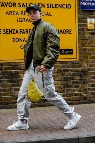 Olive Bomber Jacket Outfits For Men: Extremely dapper and functional, this off-duty combination of an olive bomber jacket and grey cargo pants delivers amazing styling opportunities. If you're clueless about how to finish off, a pair of white leather low top sneakers is a wonderful choice.