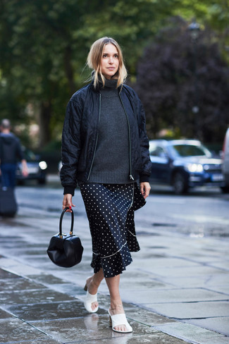 How to wear: black quilted bomber jacket, charcoal wool turtleneck, black and white polka dot midi skirt, white leather mules
