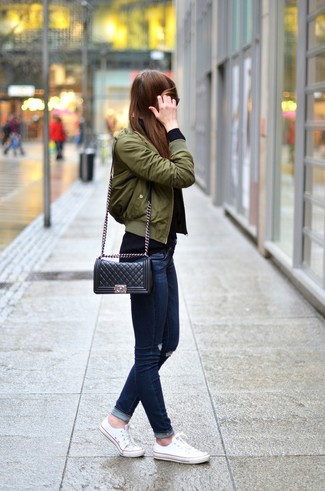 Olive Bomber Jacket Casual Outfits For Women: An olive bomber jacket and navy ripped skinny jeans teamed together are a total eye candy for those dressers who prefer relaxed getups. Introduce a pair of white canvas low top sneakers to your outfit et voila, the look is complete.
