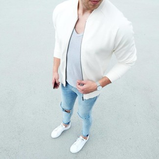 How to Wear a Grey V-neck T-shirt For Men: If you're a fan of comfort dressing when it comes to your personal style, you'll love this city casual combo of a grey v-neck t-shirt and light blue ripped skinny jeans. Avoid looking too casual by finishing with white low top sneakers.