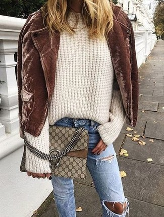 How to wear: brown suede biker jacket, beige knit oversized sweater, blue ripped jeans, brown print leather crossbody bag
