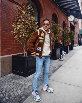 How to wear: brown fur bomber jacket, beige hoodie, light blue jeans, grey athletic shoes