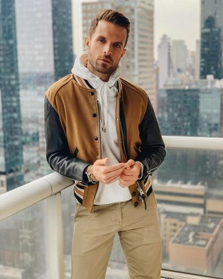 How to wear: brown bomber jacket, white hoodie, khaki chinos, brown leather watch