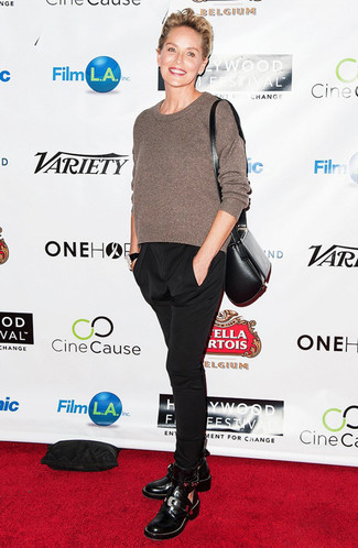 Sharon Stone wearing Brown Crew-neck Sweater, Black Tapered Pants, Black Cutout Leather Ankle Boots, Black Leather Crossbody Bag