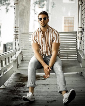 How to wear: brown vertical striped linen short sleeve shirt, grey jeans, white canvas low top sneakers, black sunglasses