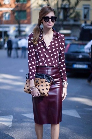 Opt for a burgundy graphic silk button front blouse and a burgundy leather pencil skirt to achieve a neat and proper look.