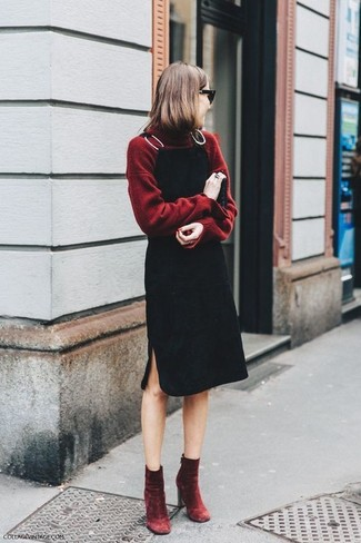 To create an outfit for lunch with friends at the weekend dress in an oxblood turtleneck and a black overall dress. Dress up this look with dark red velvet ankle boots.