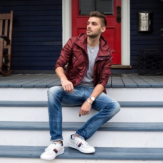 How to wear: burgundy windbreaker, grey crew-neck t-shirt, blue jeans, white leather low top sneakers