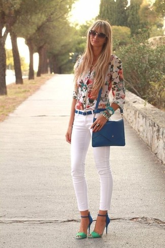 Pair a white floral button front blouse with white skinny jeans for a comfortable outfit that's also put together nicely. Finish off your look with blue suede heeled sandals.
