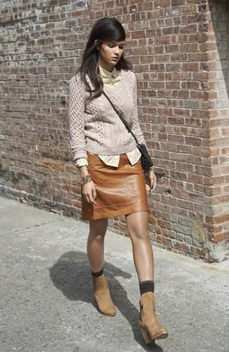 This pairing of a beige cable sweater and a brown leather mini skirt spells comfort and style. Throw in a pair of camel suede ankle boots to va-va-voom your outfit. On not-so-bone-chilling afternoons, wear a variation of this summer-to-fall outfit and look absolutely awesome.