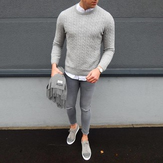 How to wear: grey cable sweater, white long sleeve shirt, grey ripped skinny jeans, grey suede low top sneakers