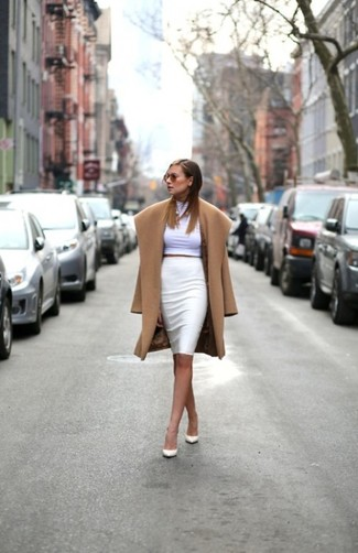 Tap into refined, elegant style with a camel coat and a white pencil skirt. This outfit is complemented perfectly with white leather pumps.