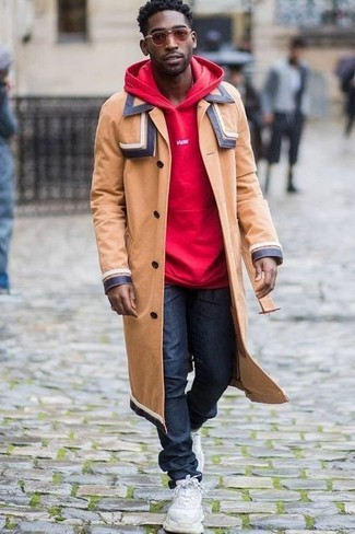 How to wear: camel overcoat, red hoodie, navy jeans, white athletic shoes