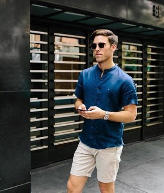 Cómo combinar: camisa de manga corta azul marino, pantalones cortos en beige, gafas de sol en marrón oscuro, reloj de lona gris