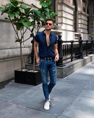 Cómo combinar: camisa de manga corta azul marino, vaqueros azules, tenis blancos, correa de cuero tejida negra