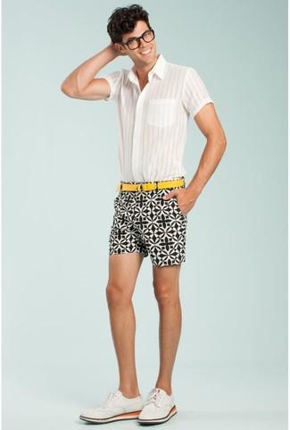 Cómo combinar: camisa de manga corta de rayas verticales blanca, pantalones cortos estampados en blanco y negro, zapatos brogue de ante blancos, correa de lona amarilla