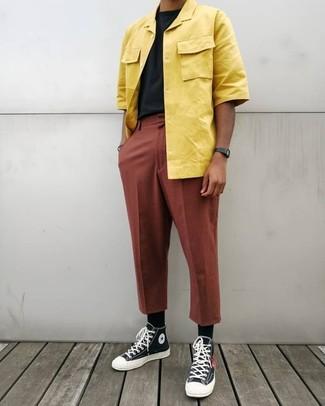 Cómo combinar: camisa de manga corta amarilla, camiseta con cuello circular negra, pantalón chino en tabaco, zapatillas altas de lona en negro y blanco