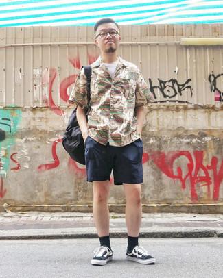 Cómo combinar: camisa de manga corta estampada marrón claro, camiseta con cuello circular blanca, pantalones cortos azul marino, tenis de lona en negro y blanco