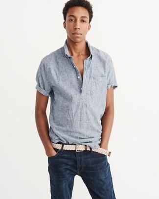 Cómo combinar: camisa de manga corta de cambray celeste, vaqueros azul marino, correa de lona tejida en beige