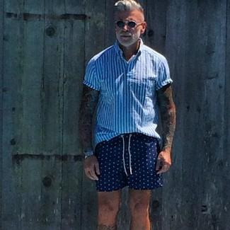 Cómo combinar: camisa de manga corta de rayas verticales en blanco y azul, pantalones cortos a lunares azul marino
