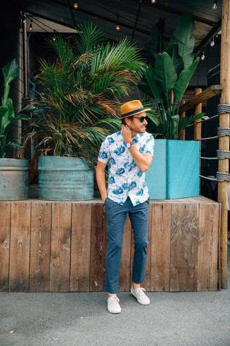 Cómo combinar: camisa de manga corta con print de flores en blanco y azul, pantalón chino azul marino, zapatillas plimsoll en beige, sombrero de paja marrón claro