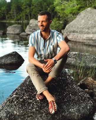 Cómo combinar: camisa de manga corta de rayas verticales en blanco y azul, vaqueros pitillo verde oliva, zapatillas slip-on de lona estampadas en multicolor, reloj plateado