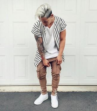 Cómo combinar: camisa de manga corta de rayas verticales en blanco y negro, camiseta con cuello circular blanca, pantalón cargo marrón, tenis de cuero blancos