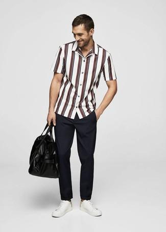 Cómo combinar: camisa de manga corta de rayas verticales en blanco y rojo, pantalón chino azul marino, tenis de cuero blancos, bolsa de viaje de cuero negra