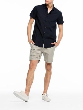 Cómo combinar: camisa de manga corta negra, pantalones cortos en beige, zapatillas plimsoll en beige