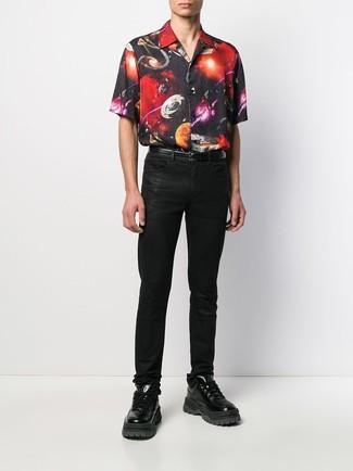 Cómo combinar: camisa de manga corta estampada negra, vaqueros negros, deportivas de cuero negras, correa de cuero negra