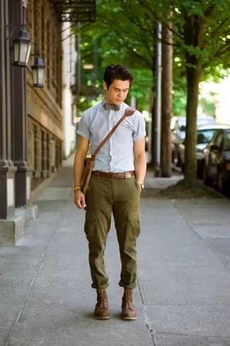 Cómo combinar: camisa de manga corta celeste, pantalón cargo verde oliva, botas casual de cuero en marrón oscuro, bolso mensajero de cuero marrón