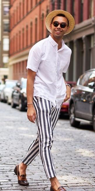 Cómo combinar: camisa de manga corta blanca, pantalón chino de rayas verticales en negro y blanco, mocasín de cuero en marrón oscuro, sombrero de paja marrón claro