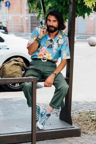 Cómo combinar: camisa de manga corta con print de flores azul, pantalón chino verde oscuro, zapatillas altas de lona azules, bolsa tote de lona verde oliva