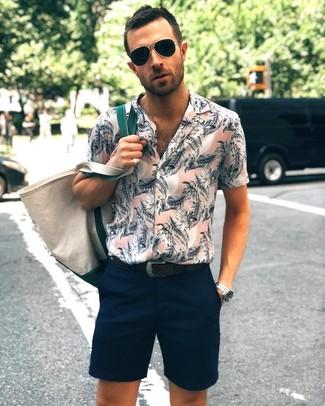 Cómo combinar: camisa de manga corta con print de flores rosada, pantalones cortos azul marino, bolsa tote de lona en beige, correa de cuero negra