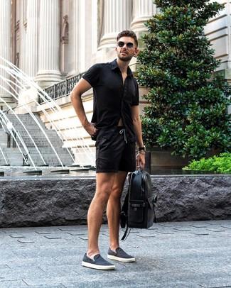 Cómo combinar: camisa de manga corta negra, pantalones cortos negros, zapatillas slip-on de lona azul marino, mochila de cuero negra