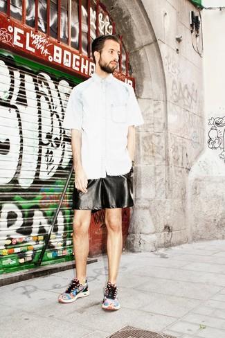 Cómo combinar: camisa de manga corta vaquera celeste, pantalones cortos de cuero negros, deportivas estampadas en multicolor