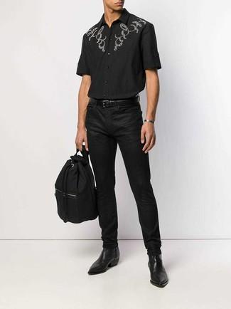 Cómo combinar: camisa de manga corta bordada negra, vaqueros negros, botines chelsea de cuero negros, mochila de lona negra