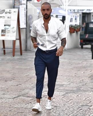 Cómo combinar: camisa de manga larga blanca, pantalón chino de rayas verticales azul marino, tenis blancos, correa de cuero azul marino